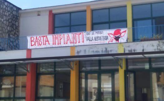 """I carabinieri della stazione di Pignataro Maggiore hanno fatto rimuovere uno striscione ambientalista dalla facciata della scuola e convocato la preside in caserma quale """"persona informata sui fatti"""" – I cittadini la accolgono con gli applausi"""